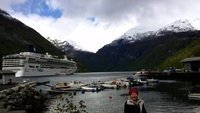 "My ""cool"" wife on shore in Geiranger with the port, ship and tenders."