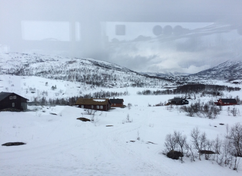 View through coach window on top of snowy mountains at Eidfjord