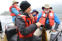 Expedition leader Pam with adventurers on a Zodiak, describing the wonders of kelp.
