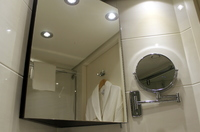 Bathroom mirrors - bathrobe hung on the door.  There is a cabinet behind