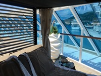 Outdoor day bed poolside at the back of the ship with elegant white drapes.
