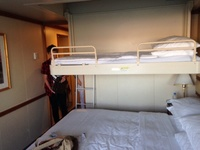 Bed lowers from ceiling and is over the main bed (may as well be a bunk bed