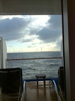 "Our veranda w ""long chairs, aka chaise lounges. View of wind farm."