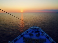 Sunset beyond the bow of TUI Discovery.