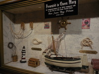 A displayed collection of maritime gifts received by Queen Mary herself add