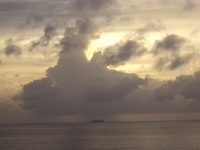 Ship in distance under cloud