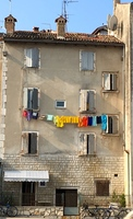 Colorful laundry line hanging from a line outside the 2nd story window.