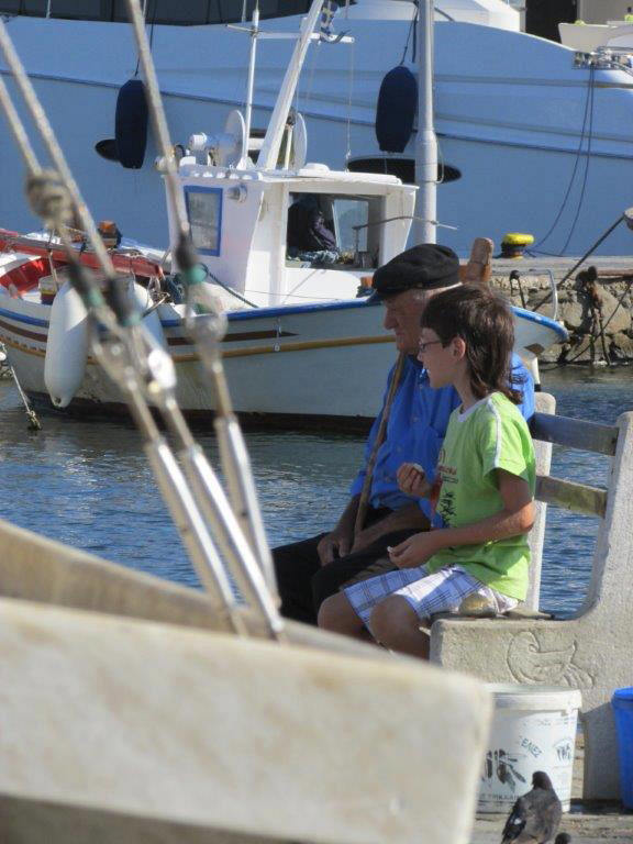 Young boy and his Grandpa sitting at the harbor in Mykonos, Greece