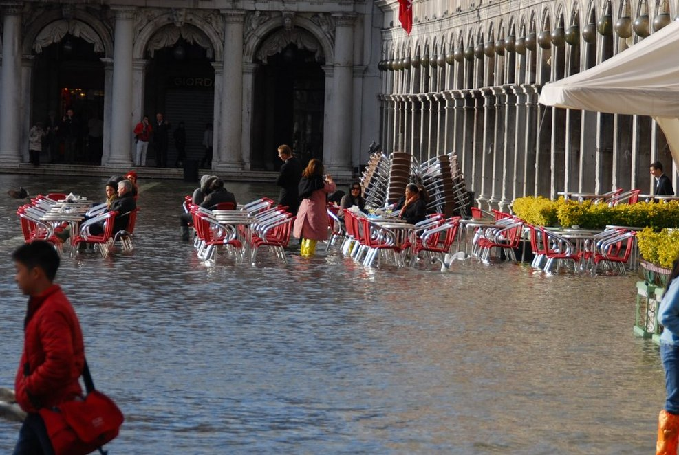 People enjoying their day at an outdoor cafe in St Marks Square in Venice during the flooding season