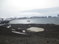 At the top of the volcano crater on Deception Island. Midnatsol in the bay.