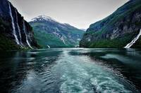 cruising up the Fjord enjoying the many waterfalls .