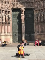 Cellist plays in front of Strasbourg Cathedral