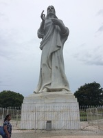 Christ's statue on a hill next to the water.