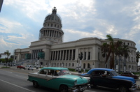 Old cars driving by the Capitol building in Havana