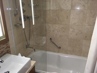 Bathroom with single sink and shower above bath. Very small as it has 2 doo