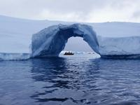 An Arch in an Iceberg with fellow passengers in a Zodiac on the other side