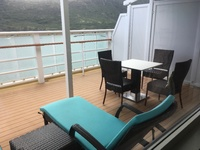 Balcony with two lounge chairs with nice cushions. Also table with four cha