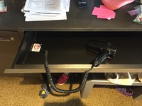 Oddly, the hair dryer is permanently attached to the desk with no signs poi