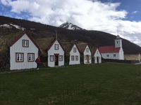 Old turf farmhouse and church in Akureryi