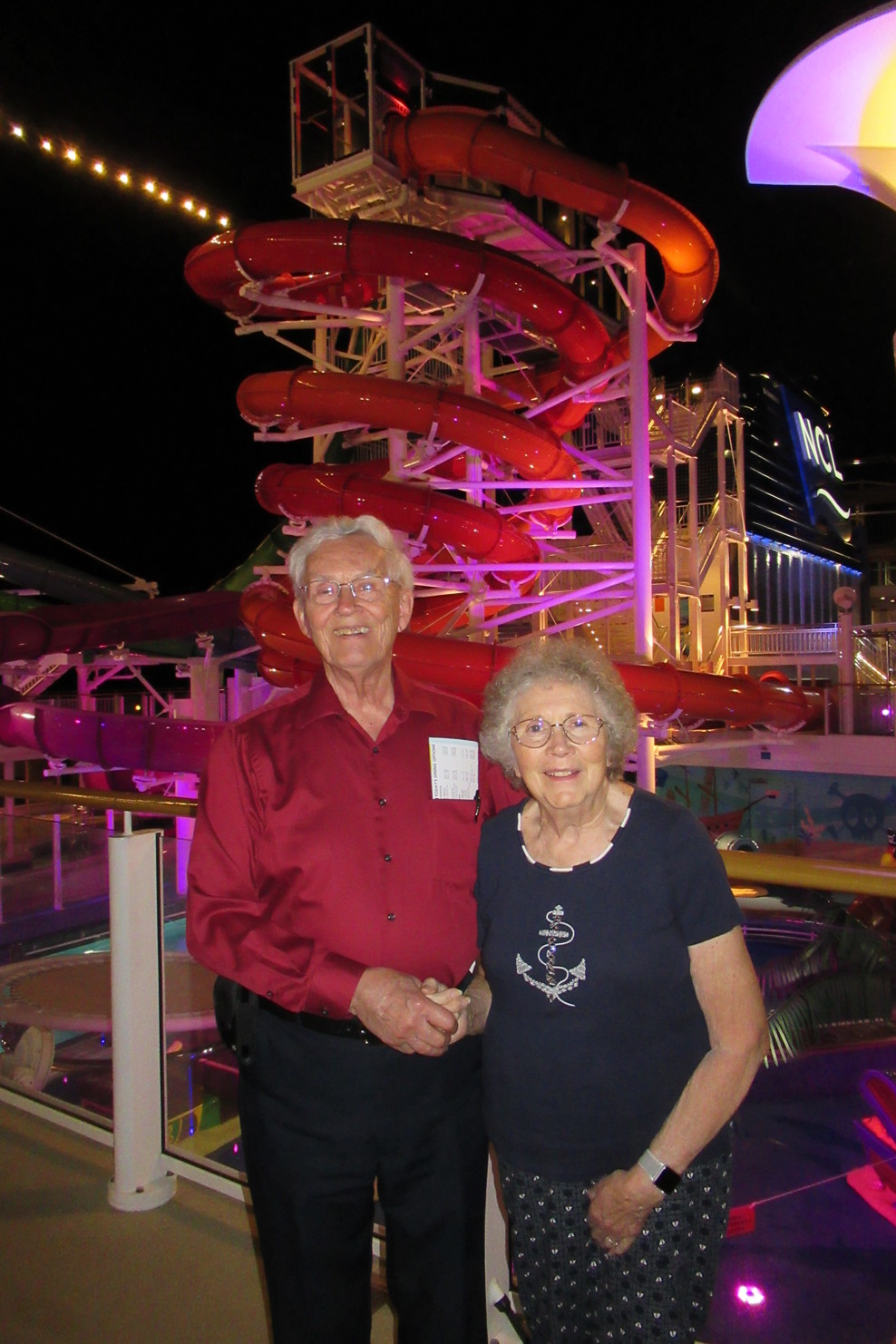 My parents on deck 16 with water slides behind them.