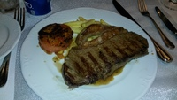 NY strip steak served in dining room with huge piece of fat on the steak