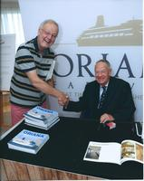 Ian Gibb signing copies of a recently published book on Oriana