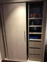 One side of closet with drawers, shelves and safe