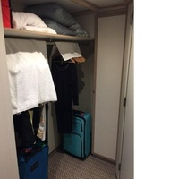 Open closet with towels on the hangers to stop the banging.