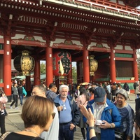 Tour participants at a busy shrine listening intently to the tour guide.
